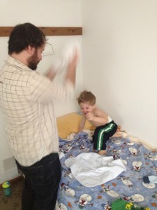 Zakk trying to dress a squirming, giggling Ben